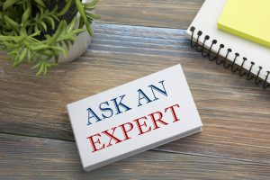 Ask an expert. Business card with message, notepad and flower. Office supplies on desk table top view